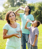 Happy couple with teenager drinking from bottles — Stock Photo