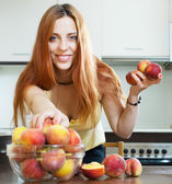 Long-haired girl taking peaches — Stock Photo