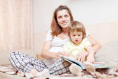 Pregnant woman and child reads book — Stock Photo