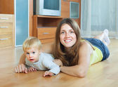 Happy mother and child on wooden floor — Stock Photo
