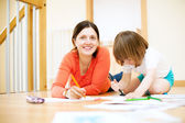 Happy mother and her child sketching on paper — Stock Photo