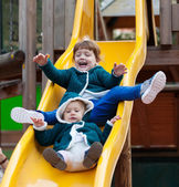 Two children on slide at playground — Stock Photo