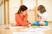 Mother and baby drawing on floor — Stock Photo