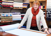 Mature saleswoman measures the fabric — Stock Photo