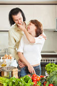 A man and a beautiful woman with vegetables in the kitchen — Stock Photo