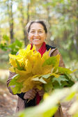Mature woman in autumn with maple posy — ストック写真