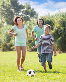 Family of three playing in soccer — Stock Photo