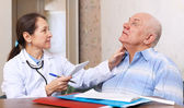 Mature doctor touching neck of man — Stock Photo