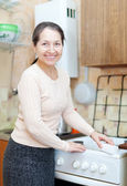 Woman cleans gas-stove with sponge in kitchen — Stockfoto