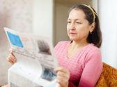 Mature woman reading newspaper — Stock Photo