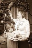 Retro photo of grandmother and baby decorating Christmas — Stock Photo