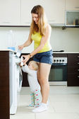 Smiling woman and child using washing machine — Stock Photo