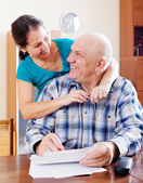 Happy mature couple fills in paper — Foto de Stock