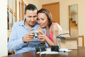 Couple unpacking new compact digital camera — Stock Photo