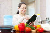 Woman cooking with cookbook in the kitchen — Stock Photo