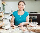 Smiling mature woman making meat dumplings — Stock Photo