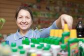 Gardener chooses liquid fertilizer at store — Stock Photo