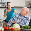 Happy playing mature couple in home kitchen — Stock Photo