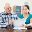 Senior man with mature woman fills in questionnaire — Stock Photo