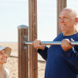 Mature couple training with chin-up bar — Stock Photo #40789715