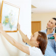 Middle-aged man and woman hanging art picture in frame — Stock Photo