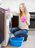 Long-haired woman doing laundry with detergent — Stock Photo