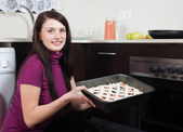 Woman putting fish pie on roasting pan into oven — Stock Photo
