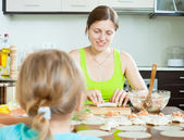 Woman with an obedient child making fish salmon dumplings — Stock Photo