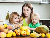 Ordinary woman with daughters eating fruits — Stock Photo
