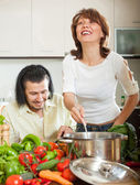 Handsome man and a young woman with vegetables in the kitchen — Stock Photo