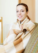 Girl warming in plaid at home — Stock Photo