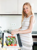 Pregnant housewife cooking trout fish — Stock Photo