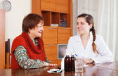 Happy doctor prescribing medication to senior woman — Stockfoto