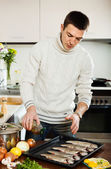 Man pouring oil in raw fish on roasting pan — Stock Photo