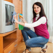 Stock Photo: Womcleaning TV with cleanser
