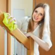 Stock Photo: Pretty girl dusting stair railings