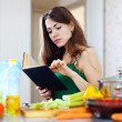 Pensive housewife with cookbook — Stockfoto