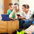 Stock Photo: Happy family of three reserving hotel on internet using laptop