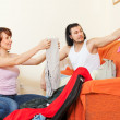 Couple sitting on sofa and packing suitcase — Stock Photo #40790901