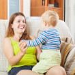 Happy mom with child on sofa — Stock Photo #40791189