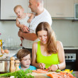 Family of four red cooking salmon on the home kitchen — Stock Photo #40791389