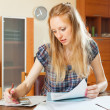 Serious blonde woman fills in documents — Stock Photo
