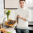 Handsome man holding raw trout — Stock Photo