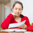 Mature woman reads payment documents — Stock Photo