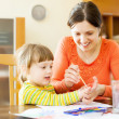 Happy mother and child drawing with hands and watercolor — Stock Photo