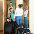 Happy family of three with teenager going with suitcases — Stock Photo
