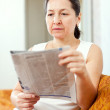 Stock Photo: Serious mature womreads newspaper