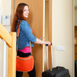 Happy red-haired woman with luggage locking door and leaving her — Stock Photo