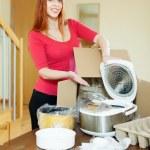 Счастливые молодые домохозяйка распаковка нового кухонного агрегата — Стоковое фото #40793143