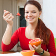 Happy beautiful woman in red eats grapefruit — Stock Photo